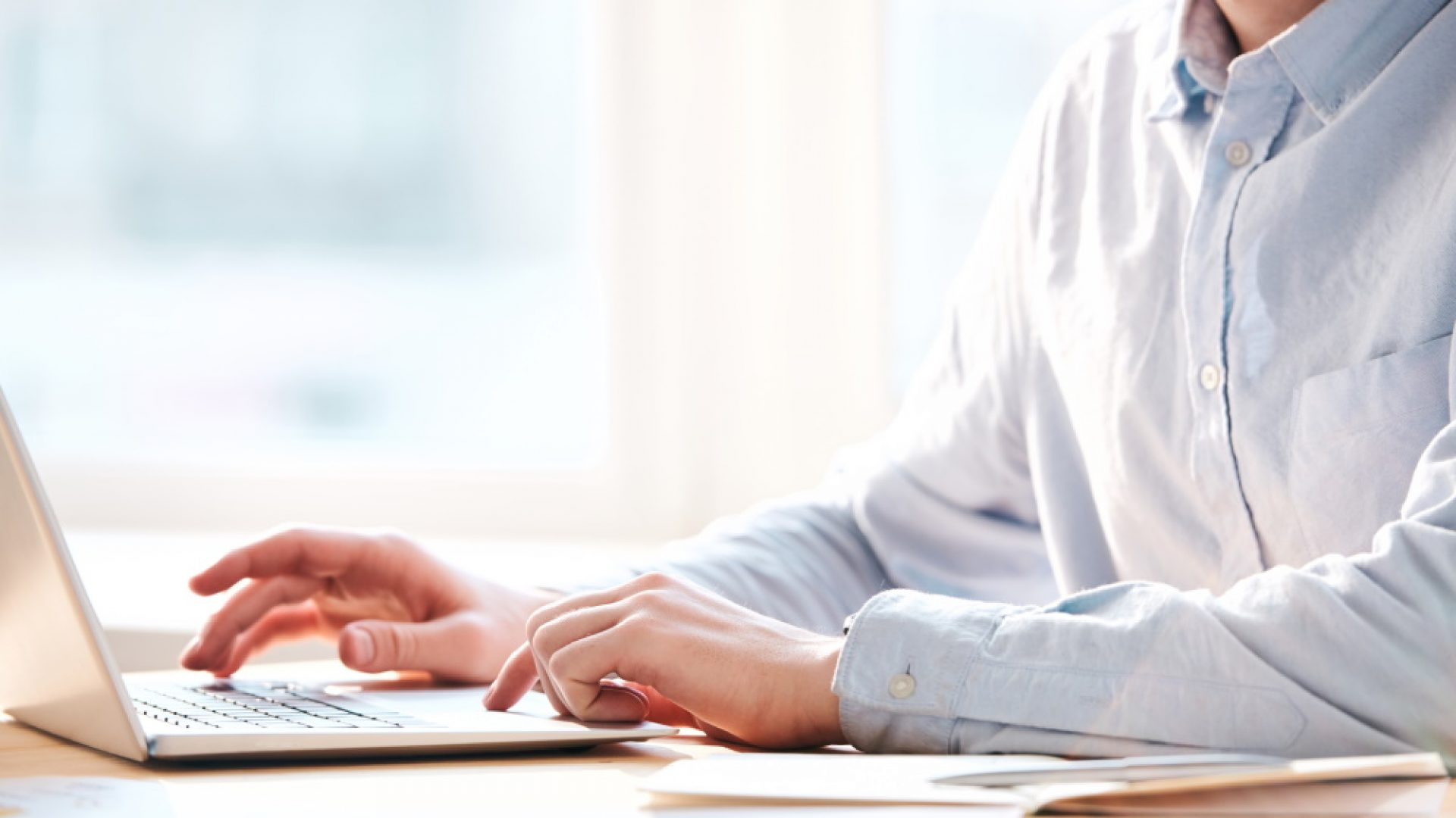 Close-up of busy man sitting at table and using laptop while analyzing internet resources